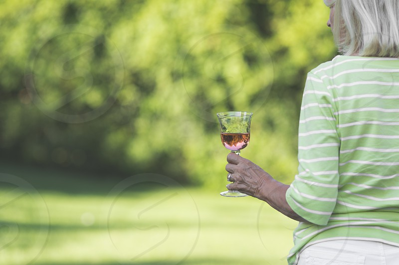 A woman holding a glass of wine outside photo