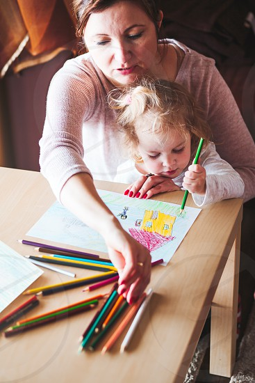 Mom with little daughter drawing a colorful pictures of house and playing children using pencil crayons sitting at table indoors photo
