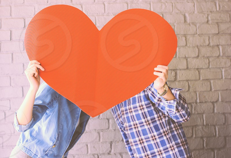 Couple holding handmade paper heart with retro filter effect photo