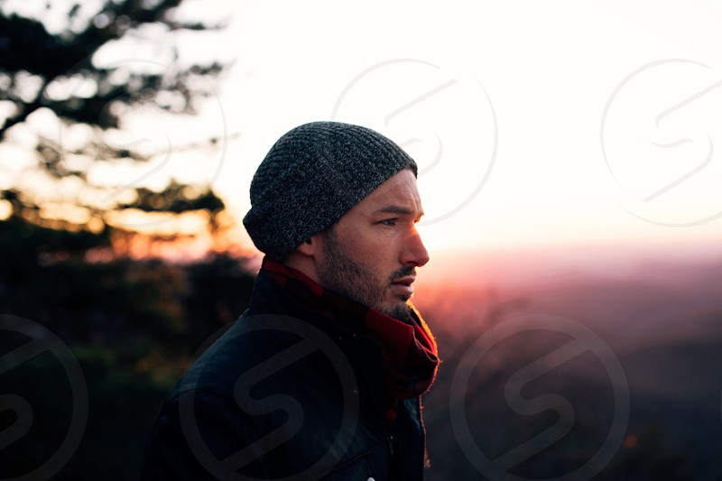 man in black and gray knit hat red scarf and coat under white sky during daytime photo