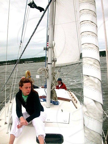 woman wearing black zip-up jacket sitting on white powerboat photo