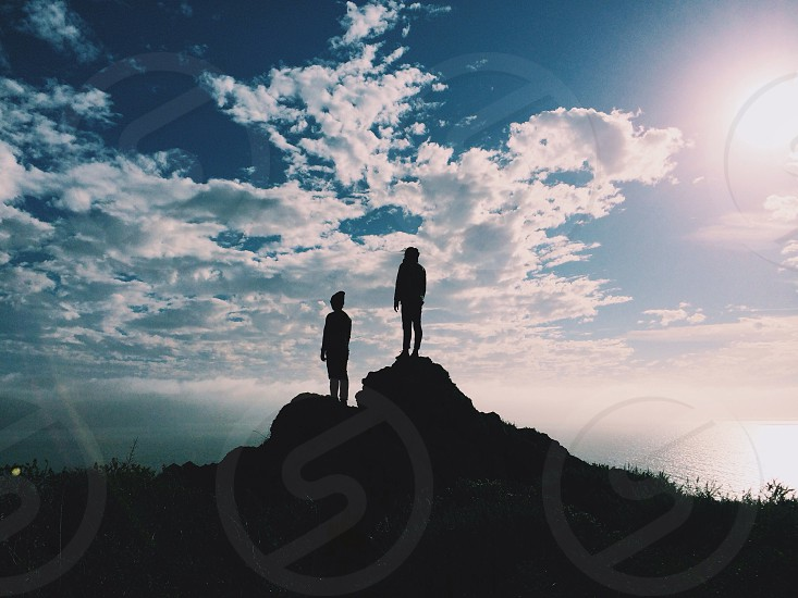 2 silhouette on rock with cloudy sky view  photo
