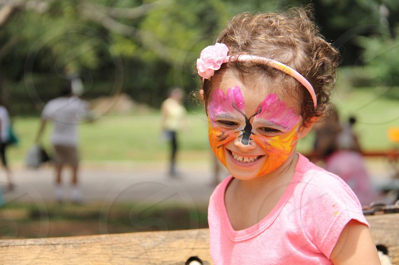 girl in pink v neck t shirt smiling with butterfly face paint photo