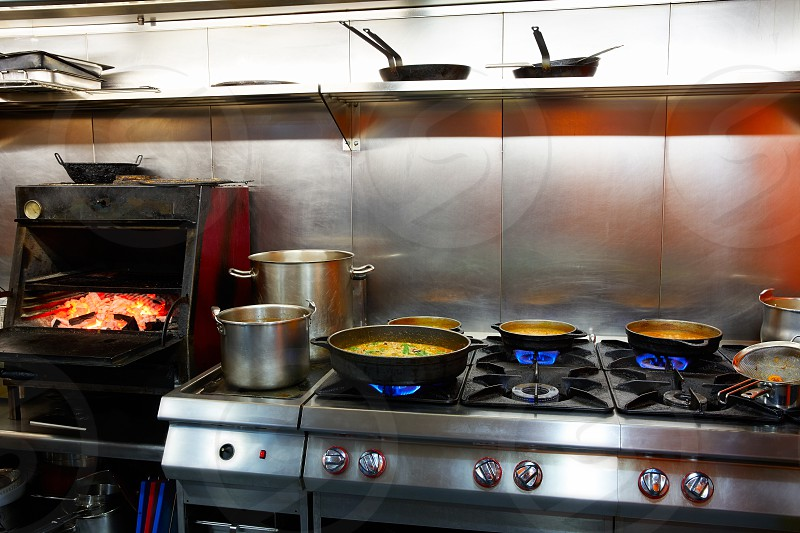 Mediterranean kitchen indoor with paella and flame grill photo