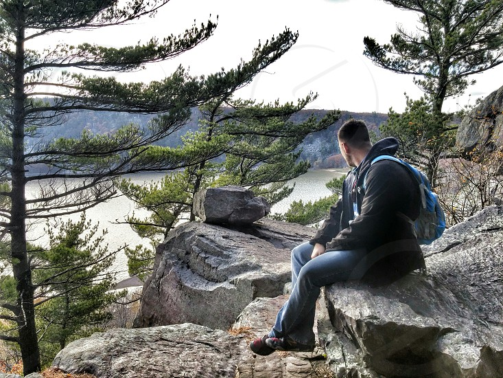 man wearing black hoodie sitting on rock formation looking at water body photo