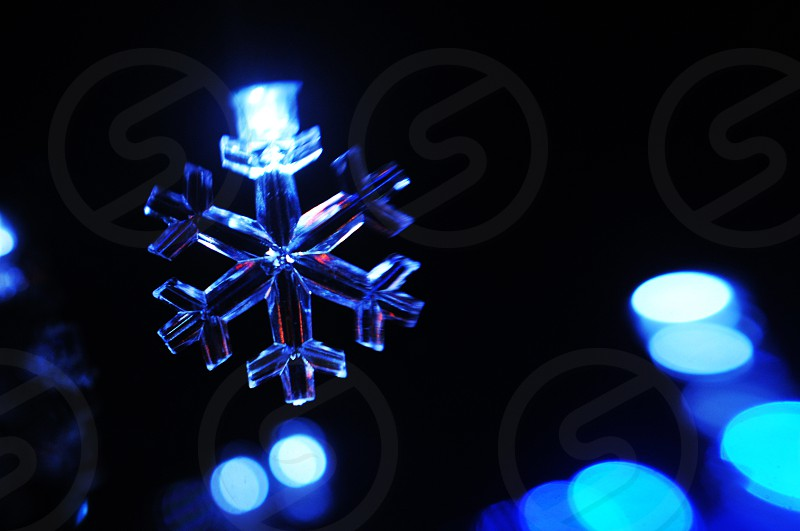 Blue glowing snowflake holiday Christmas light and bokeh photo