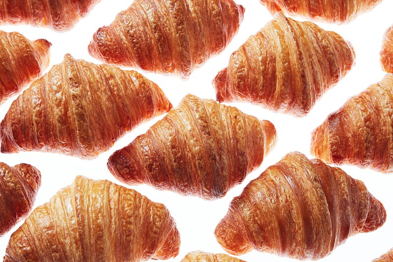 Food rhombus pattern from crunchy homemade french croissants on a light background. Close up view. photo