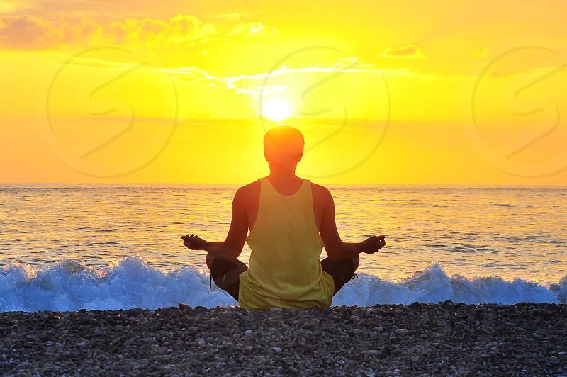 man in white tank top meditating near ocean photo