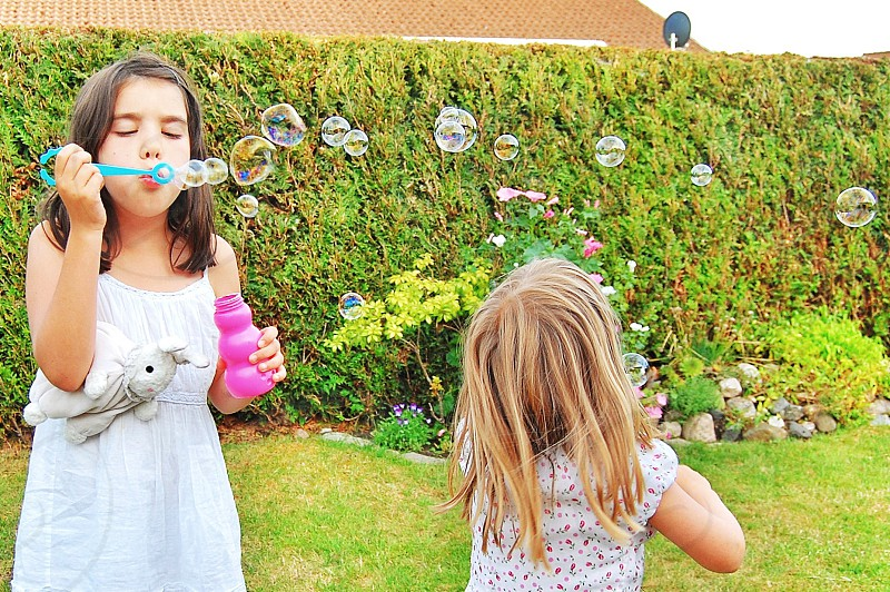 2 girls playing bubbles photo