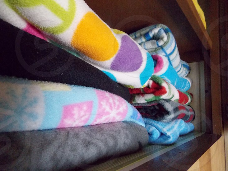 multicolored blankets on shelf photo