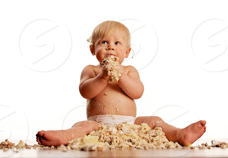 messy baby boy with cake destroyed on hard wood floor photo