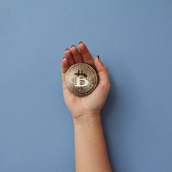 Gold coin bitcoin in a woman's hand isolated on a blue background. Cryptocurrency and blockchain concept photo