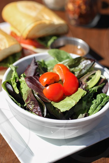 selective focus photography of water spinach topped with sliced tomato on white ceramic bowl photo