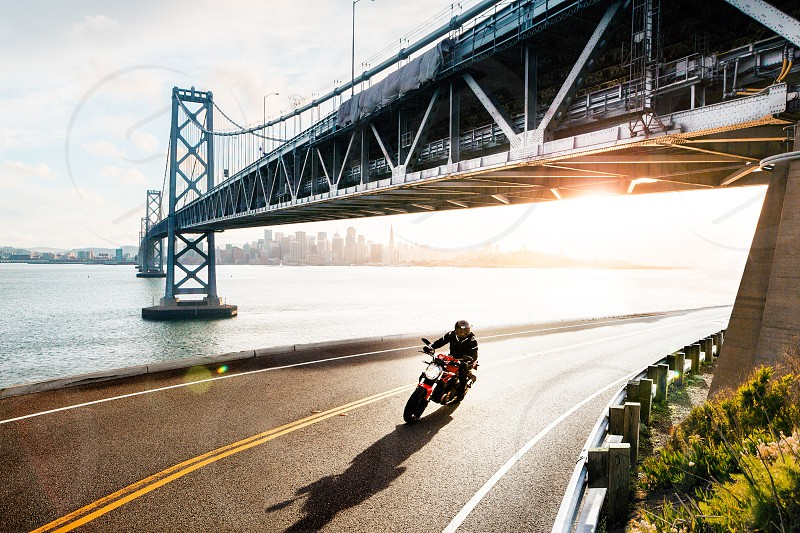 person wearing black jacket riding on motorcycle on gray rolled asphalt road photo