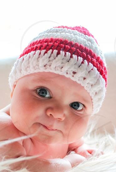 Cute baby looking at the camera wearing a striped hat photo