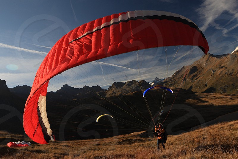 person landing with red parachute blowing photo