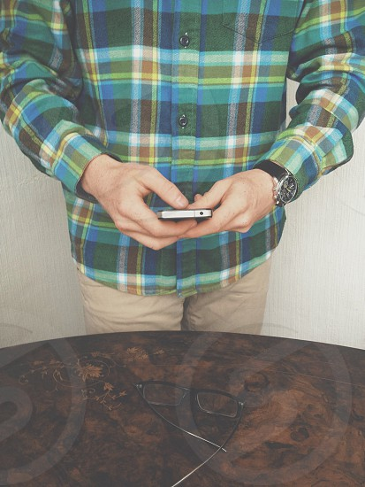 person wearing green plaid button down long sleeved shirt photo