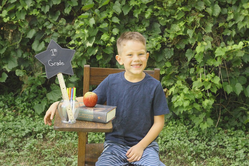 School boy kid son summer outside outdoors book Apple markers ruler sign grass grade smile smiling photo