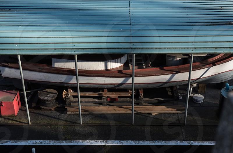 hidden underneath boat water bound blue wooden metal photo