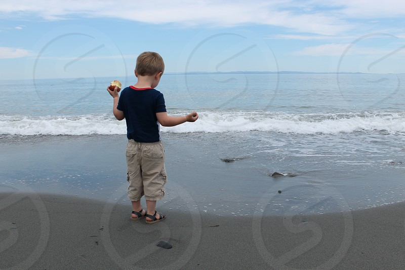 boy looking at waves holding an apple photo
