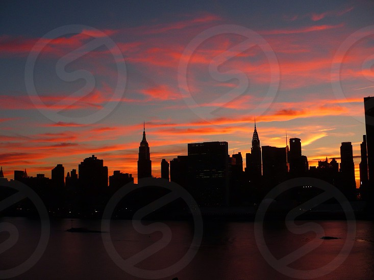 sunset over cityscape on water photo