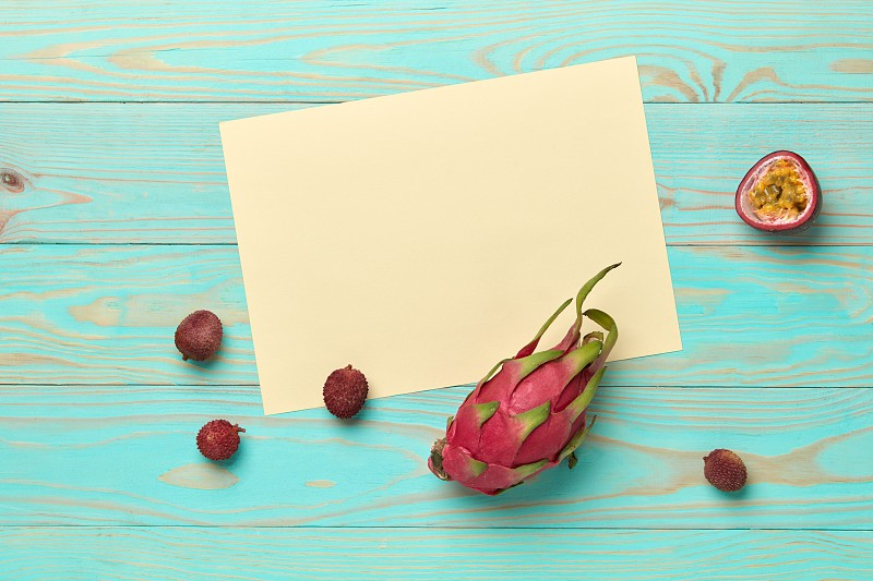 White cardboard with passion fruit pitahaya and lychee on a blue wooden background with space for text. Card. Flat lay photo