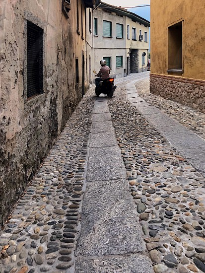 a man rides a motorbike through a small Italian street with old houses paved with cobblestones.  photo