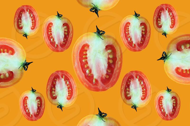 Fly of beautiful trendy seamless pattern cherry tomato isolated on orange background photo