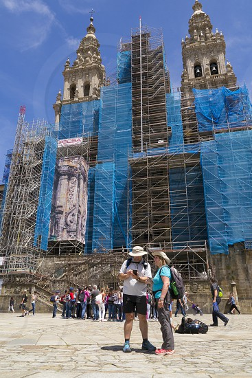 Tourists and pilgrims outside the main Cathedral in Santiago de Compostela in Galicia Spain. The cathedral is currently under-going renovation to it's facade (June 2017) photo