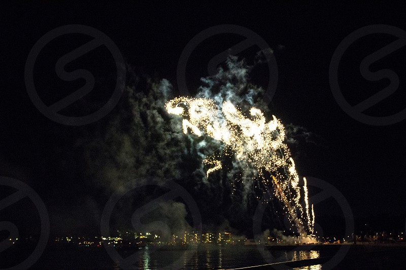 Twirling arching fireworks over lake white on black with smoke photo