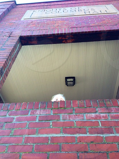Child peering from porch of a brick Knights of Columbus building photo