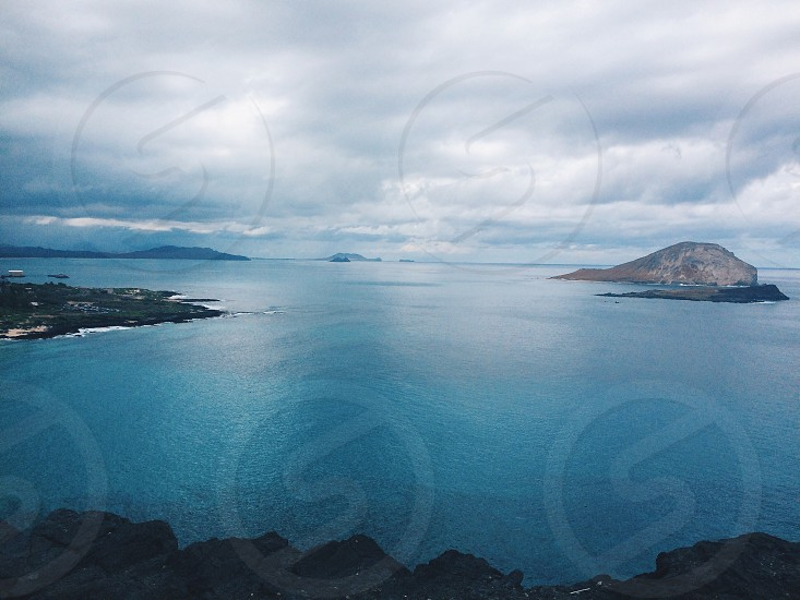 aerial angle view of sea water beside island under grey clouds during daytime photo