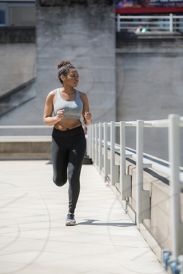 A beautiful young black woman exercising in an urban environment. photo