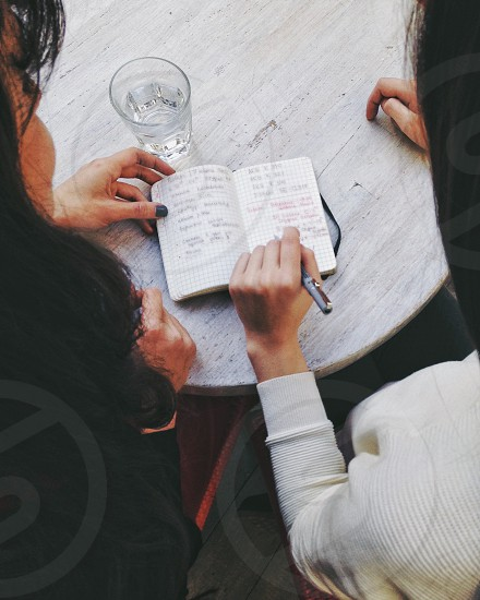 woman with black nail manicure sitting beside woman in white long sleeve shirt writing on notebook photo