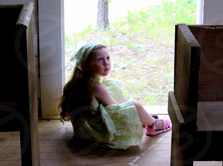 Little girl in old fashioned country style frock looking solemn sitting in back door of old church photo