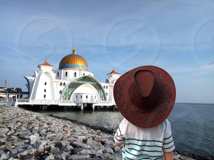 kid boy standing on seaside watching mosque photo