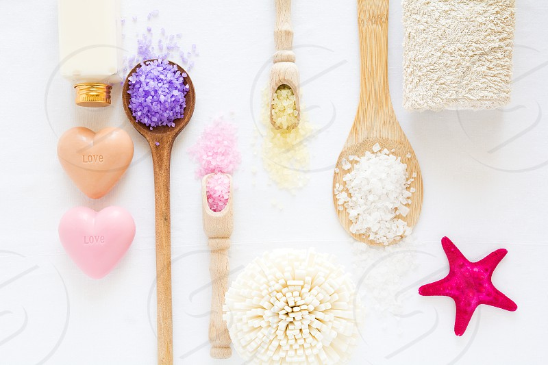 Wellness setting. Sea salt shells and soaps on white textured background. Top view. Flat lay photo