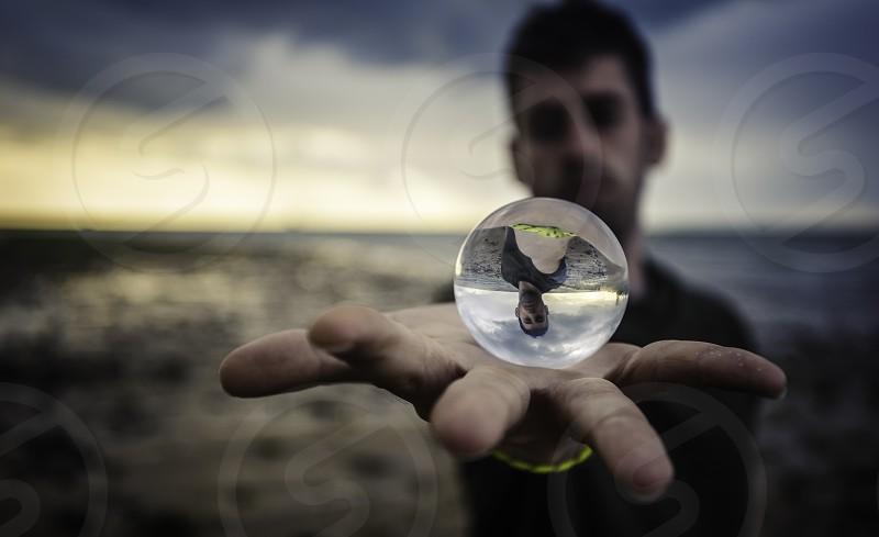 Crystal ball over the hand on the beach photo