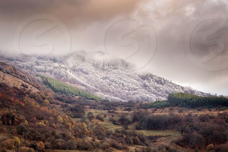 Amazing moody rocky summit covered in frost and fog autumn colors of the forest trees below on the transition period between autumn and winter  photo