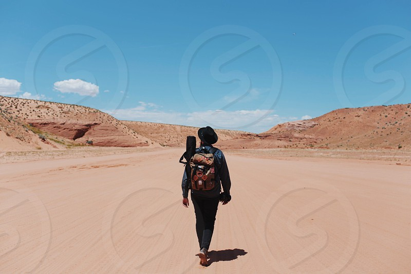 person walking in the middle of a dirt road under blue sky with white clouds during daytime photo