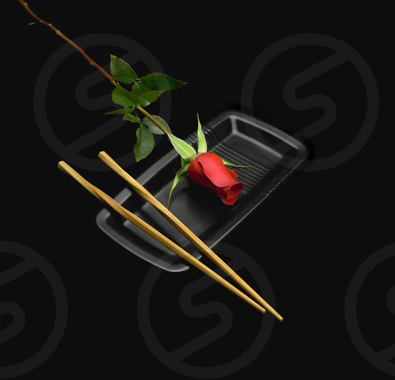 red rose on a japanese plate with chopstick over black background photo