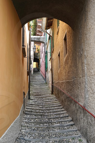 Looking up along the narrow cobbled path between buildings in an Italian village photo