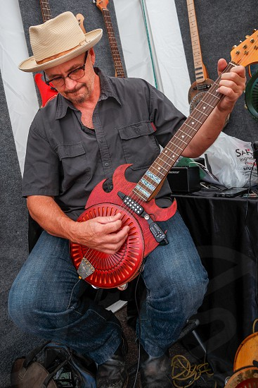 Musician plays hand made guitar at Cherry Creek Arts Festival Denver Colorado photo