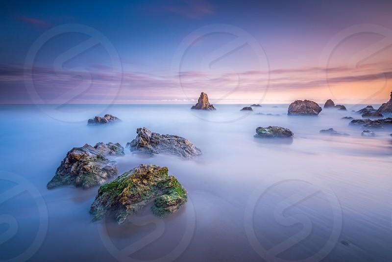 grey fogs on rocky beach under grey and blue sky photo