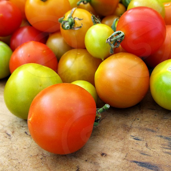 Multi-colored cherry tomatoes red yellow orange green on wood board photo