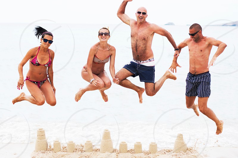 Four young people two couples jumping above sand castle on beach having summer fun. photo