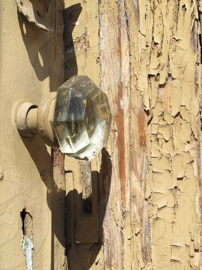 Glass door knob on old building with peeling paint photo