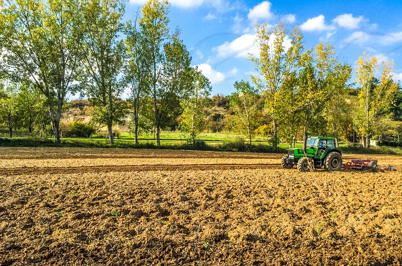 Tractor Ploughs Field In A Beautiful Rural Landscape photo