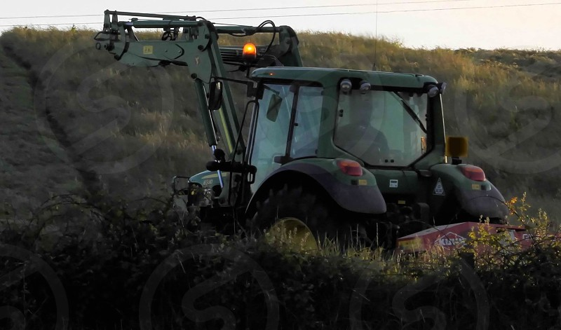 Tractor working the land in the evening sun photo