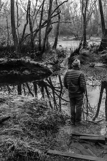 person in puffer coat near creek photo